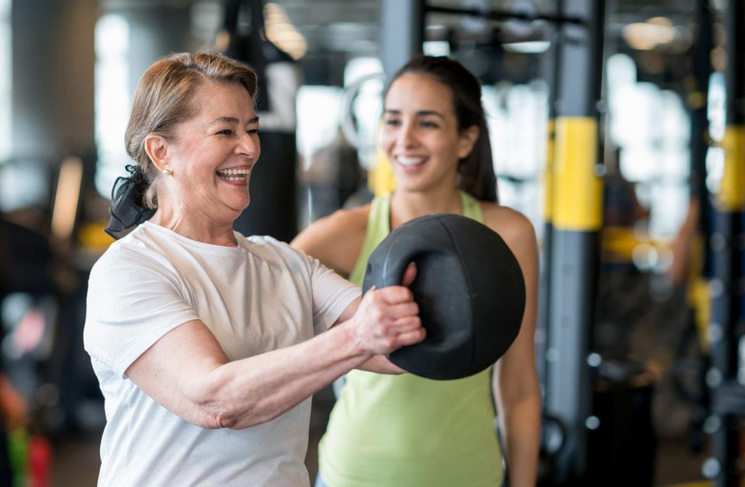 Mujer adulta haciendo ejercicio en el gimnasio con un entrenador personal y luciendo muy feliz - estilo de vida saludable