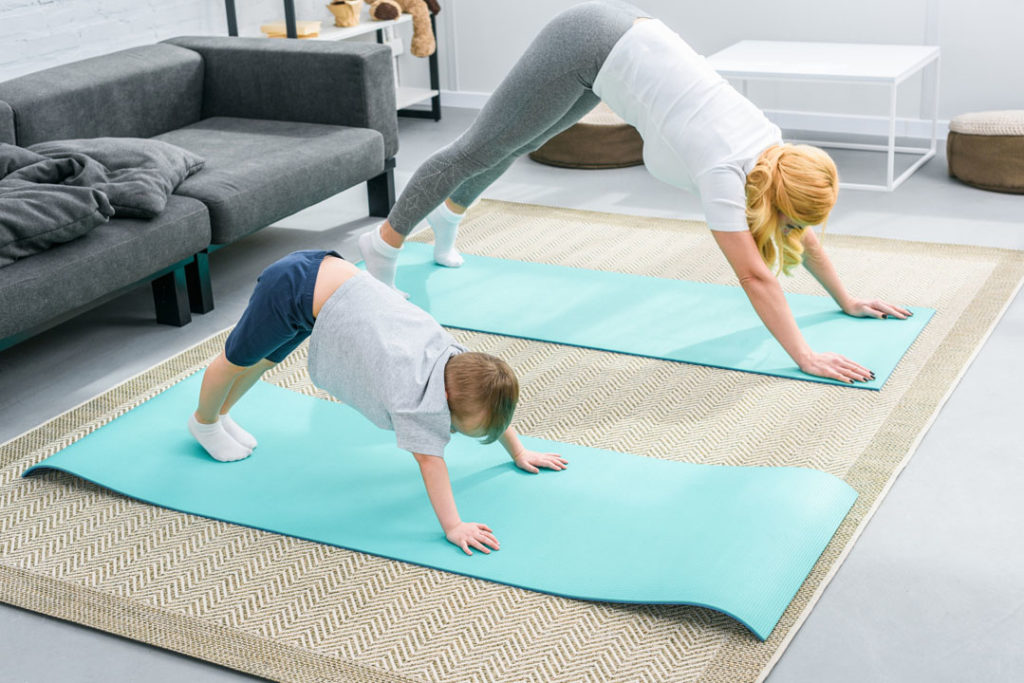 mom and young boy doing yoga at home to help boost energy and improve overall health