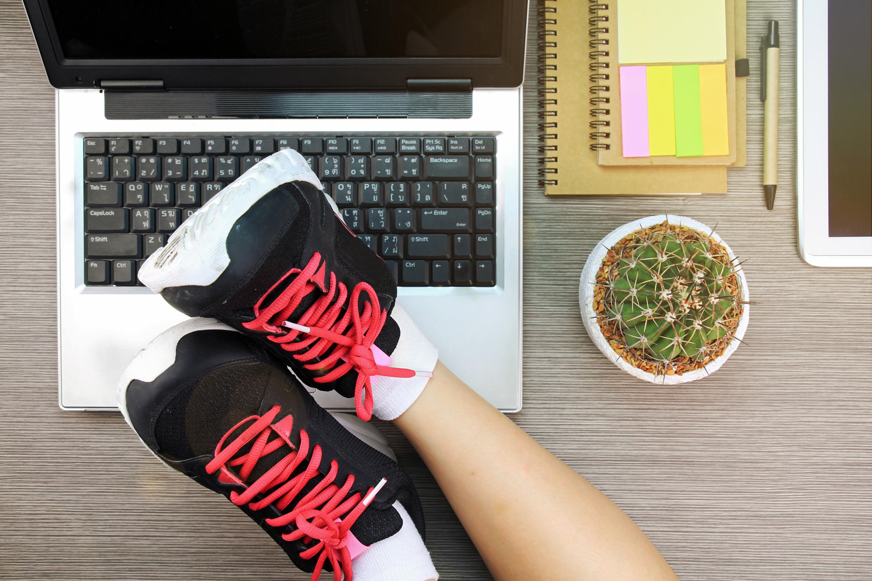 Mujeres de negocios poniendo sus piernas en calzado deportivo sobre el portátil, Concepto de equilibrio entre vida y trabajo.