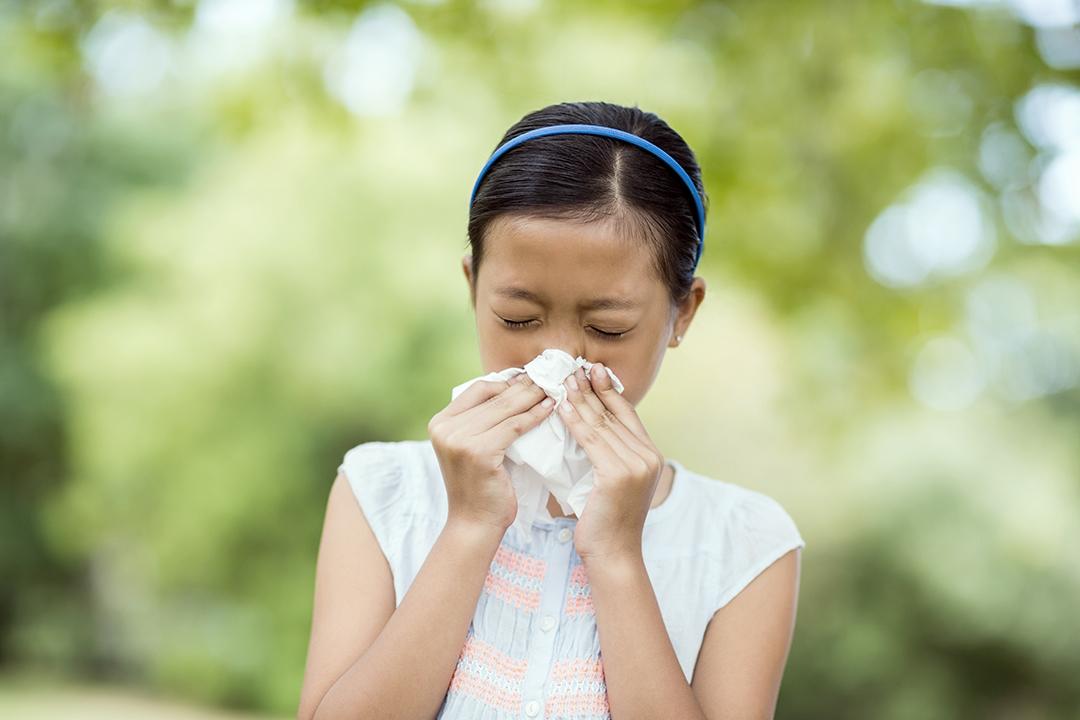 Chica sonándose la nariz con un pañuelo mientras estornuda - alergias estacionales