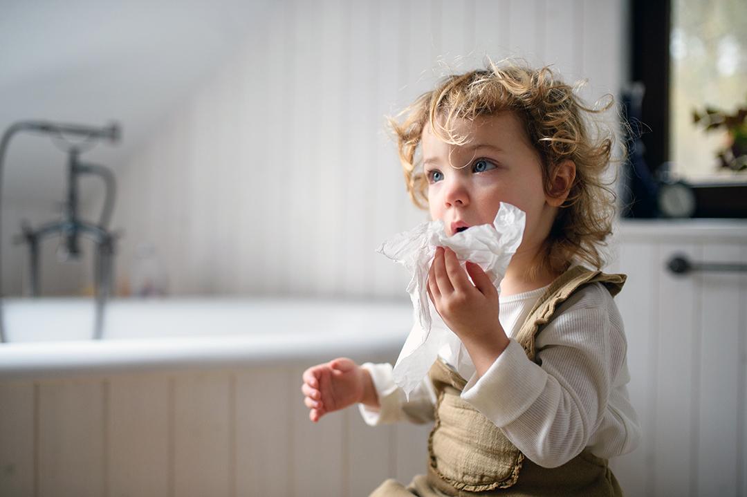 Pequeña niña enferma con resfriado en casa sentada en el suelo, sonarse la nariz.