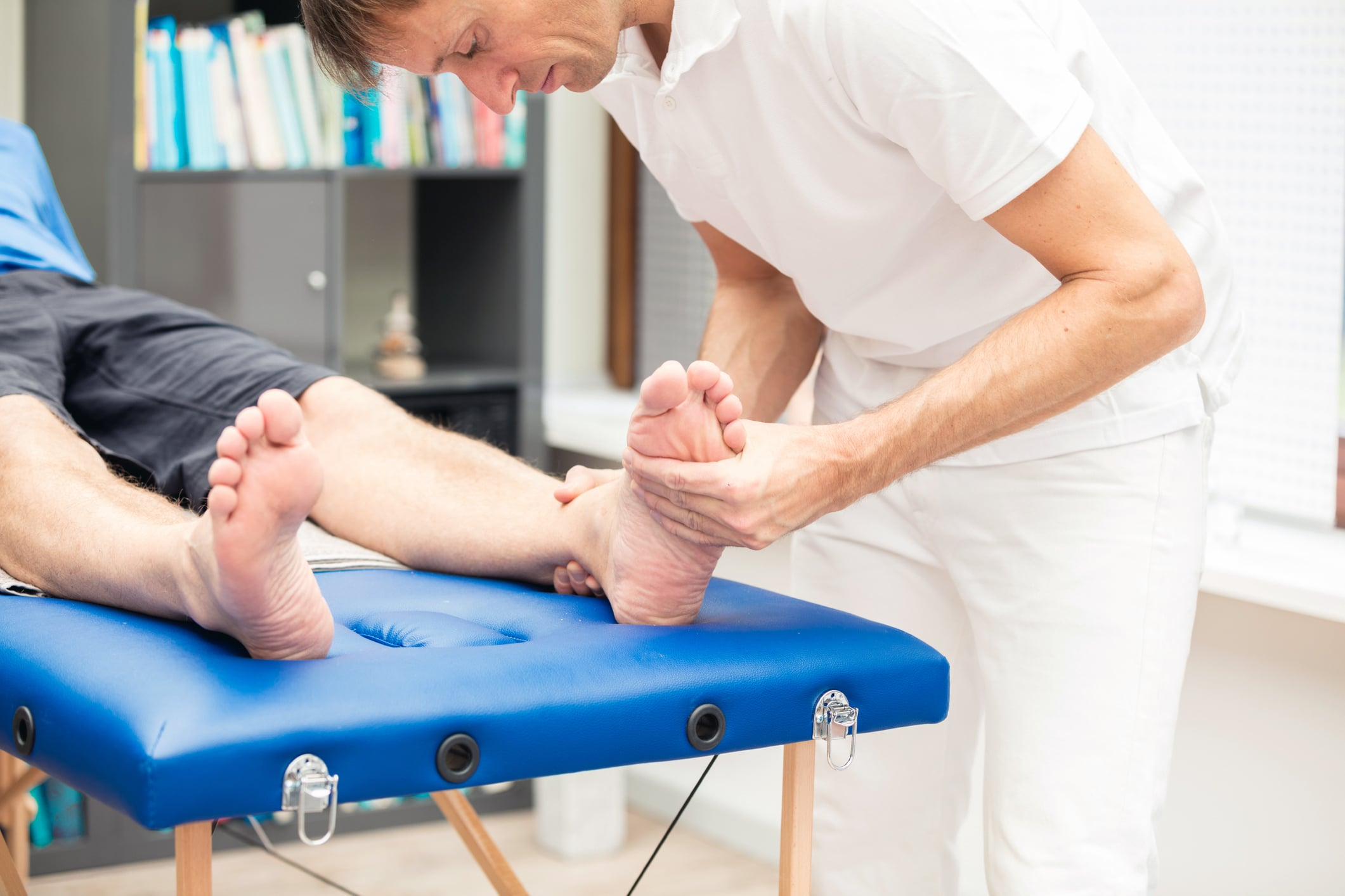 chiropractor testing foot mobility and proper support