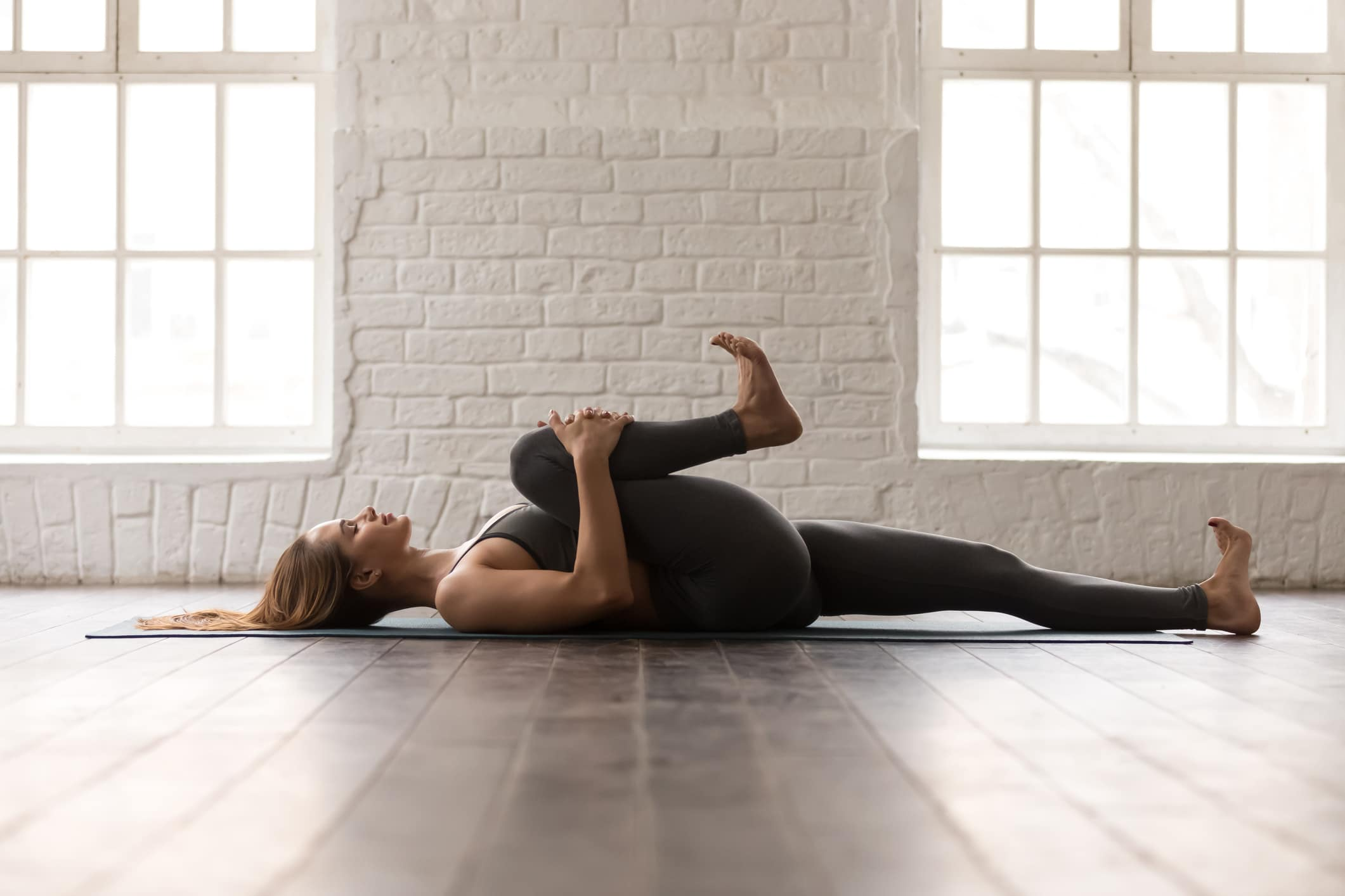 woman practicing yoga doing knee to chest squeeze