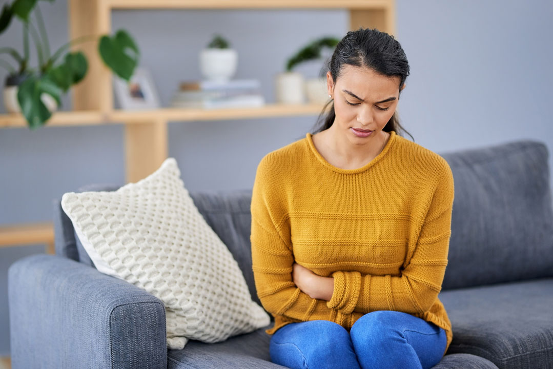 woman sitting on couch with belly bloat holding stomach looking in pain