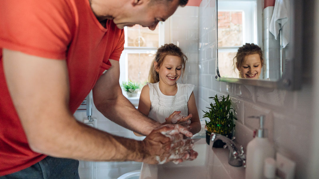 man and daughter washing hands in bathroom