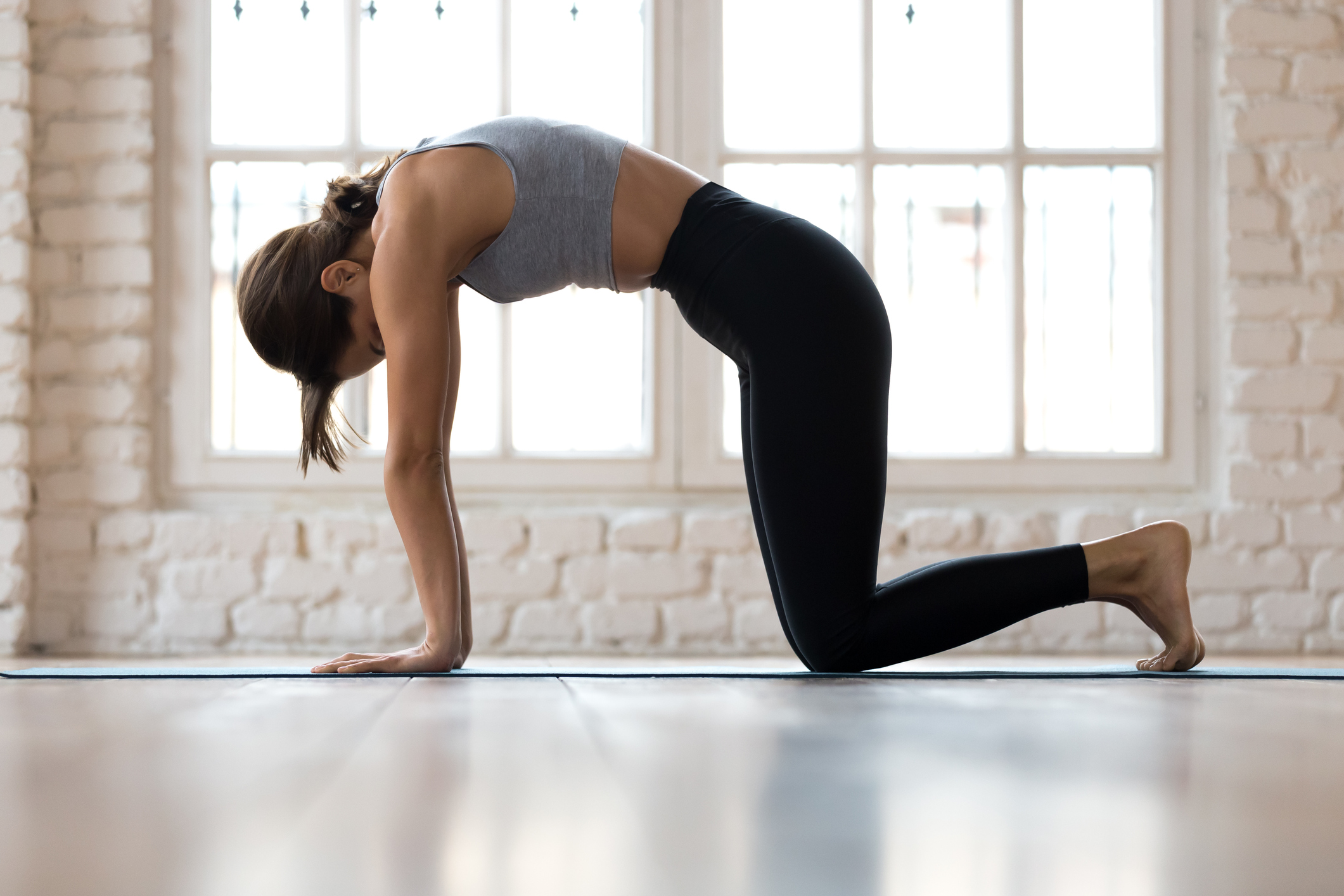 woman doing yoga cat pose exercise