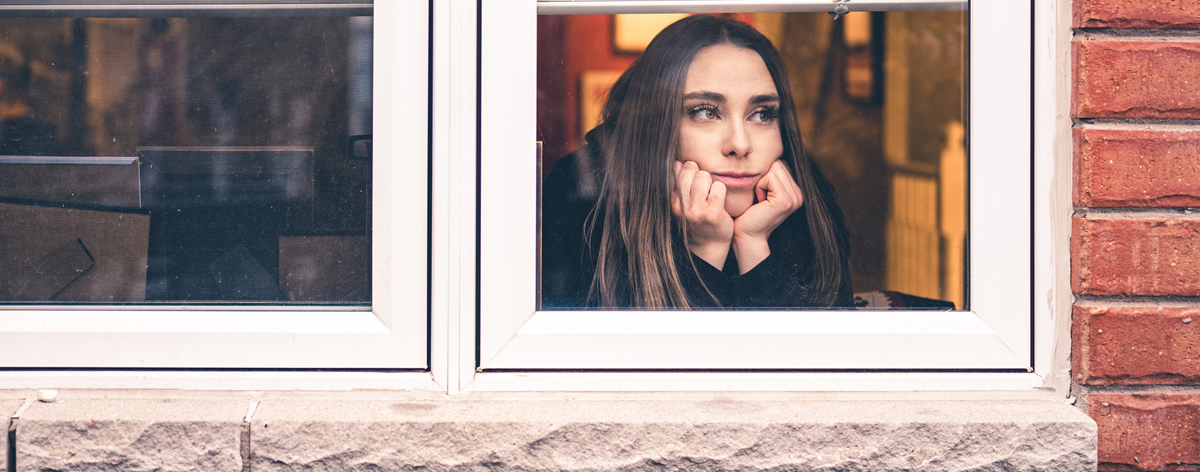 woman stay at home looking out window