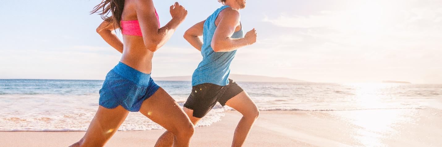 Dos adultos sanos corriendo por la mañana en la playa