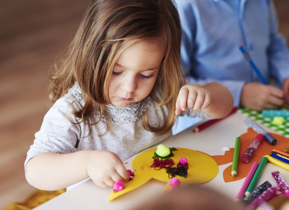 young girl doing DIY crafts from an idea box with pom pom glitter and glue