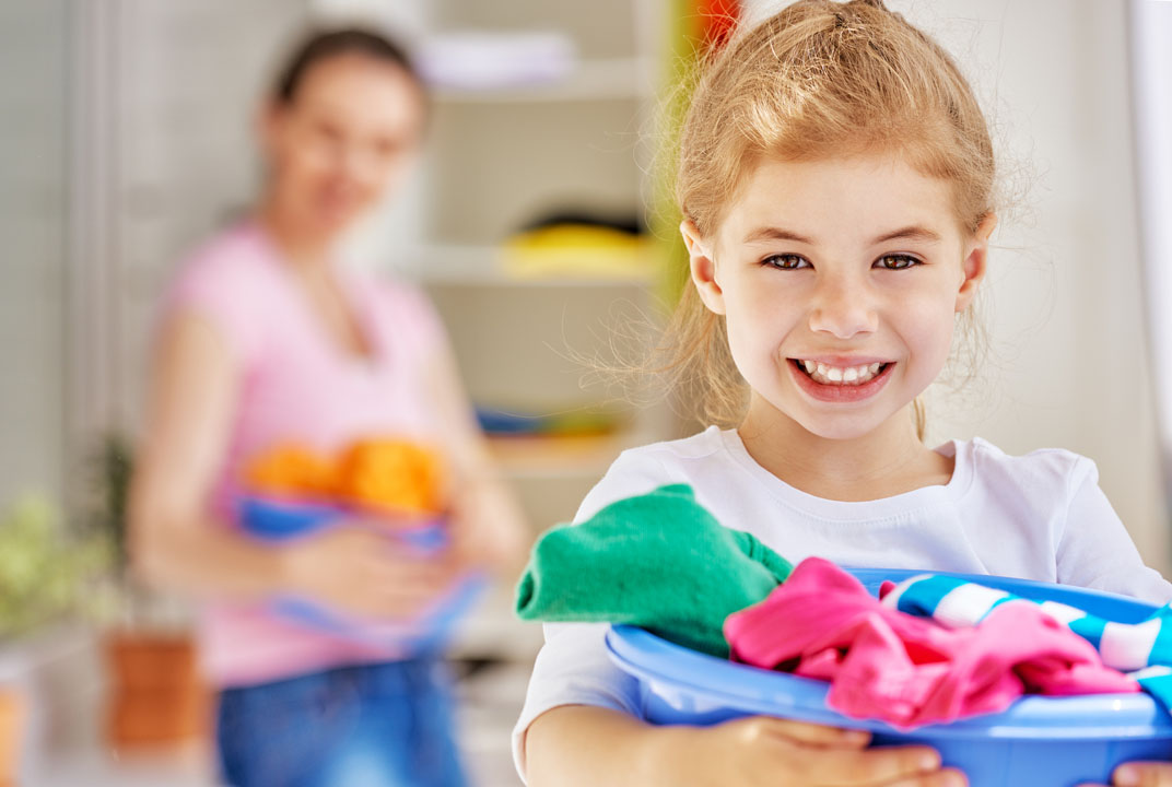 young girl helping mom with laundry chores