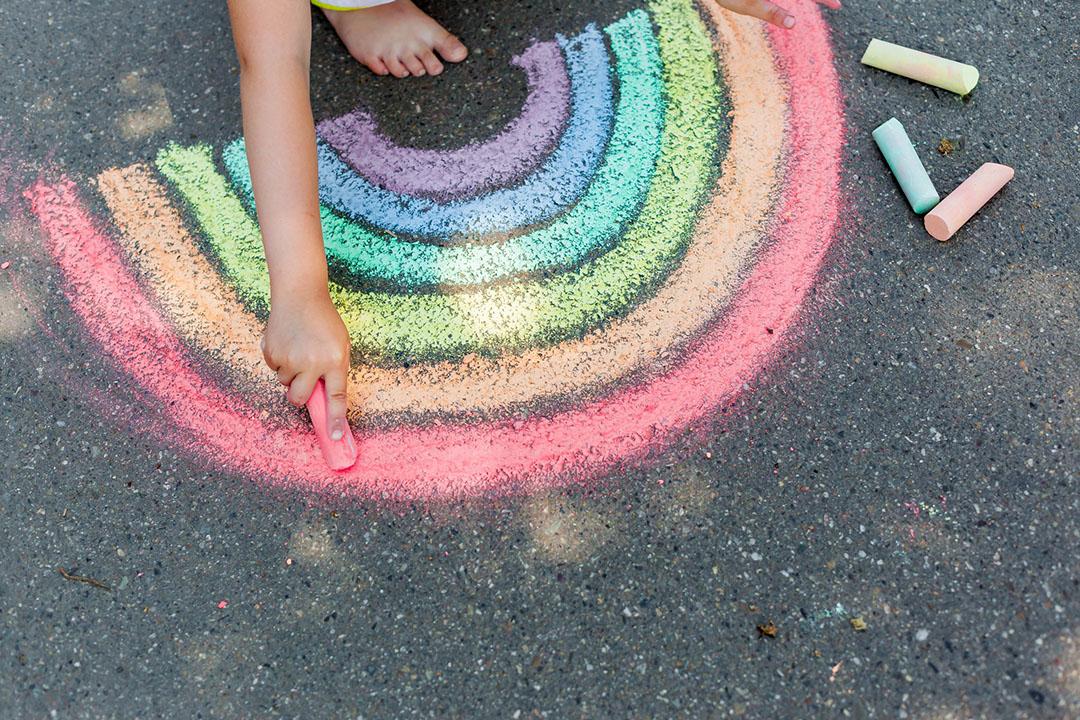 girl drawing rainbow with sidewalk chalk and sidewalk paint
