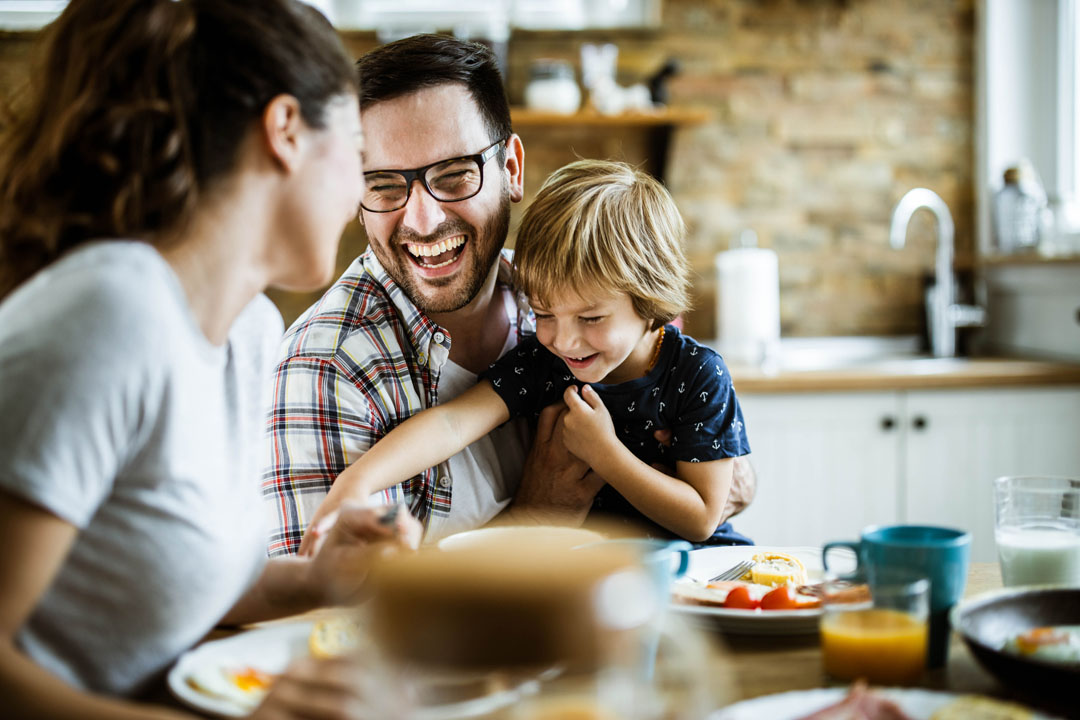 Man, wife and child - young cheerful family having fun at dining table.
