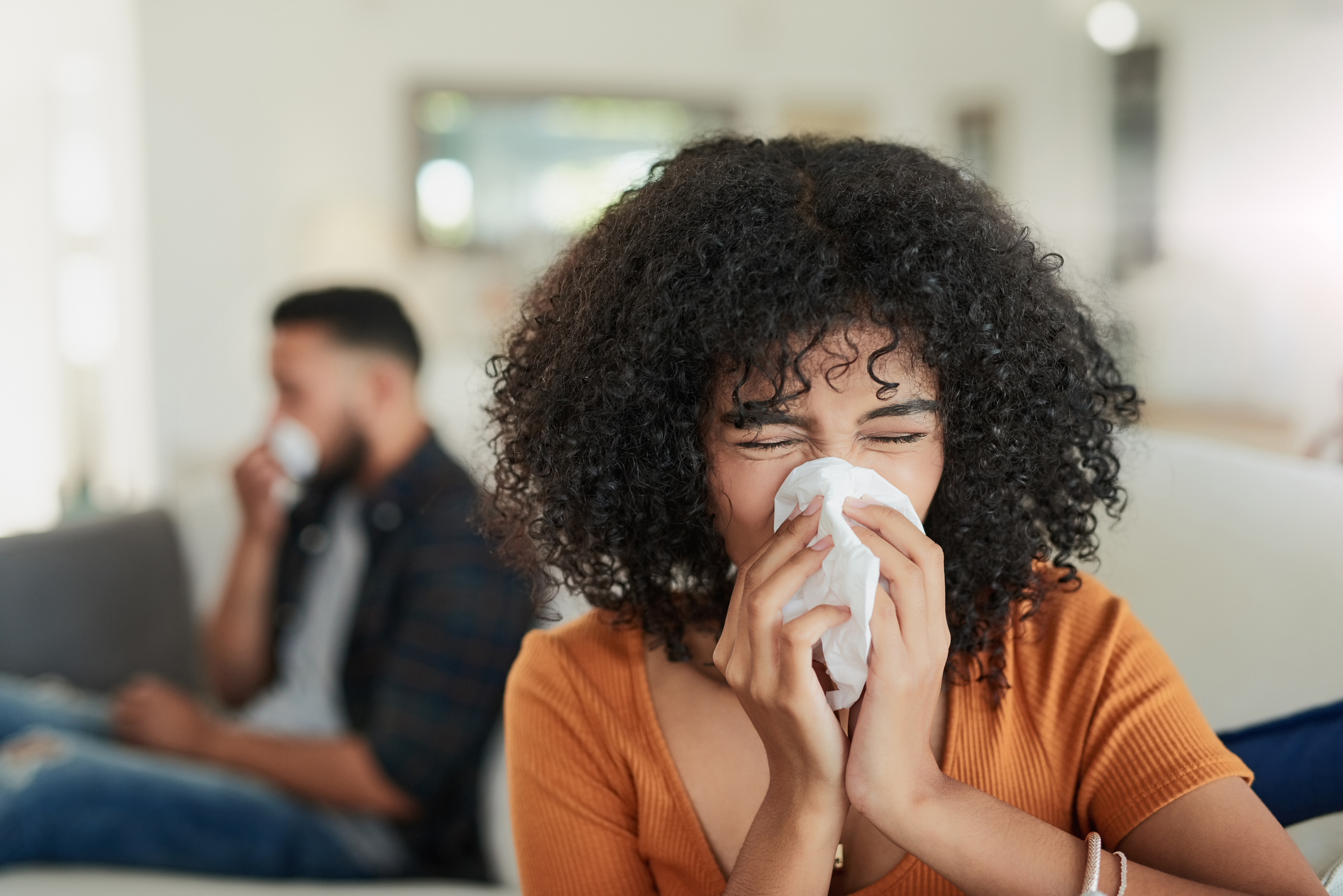 young woman blowing nose from allergies