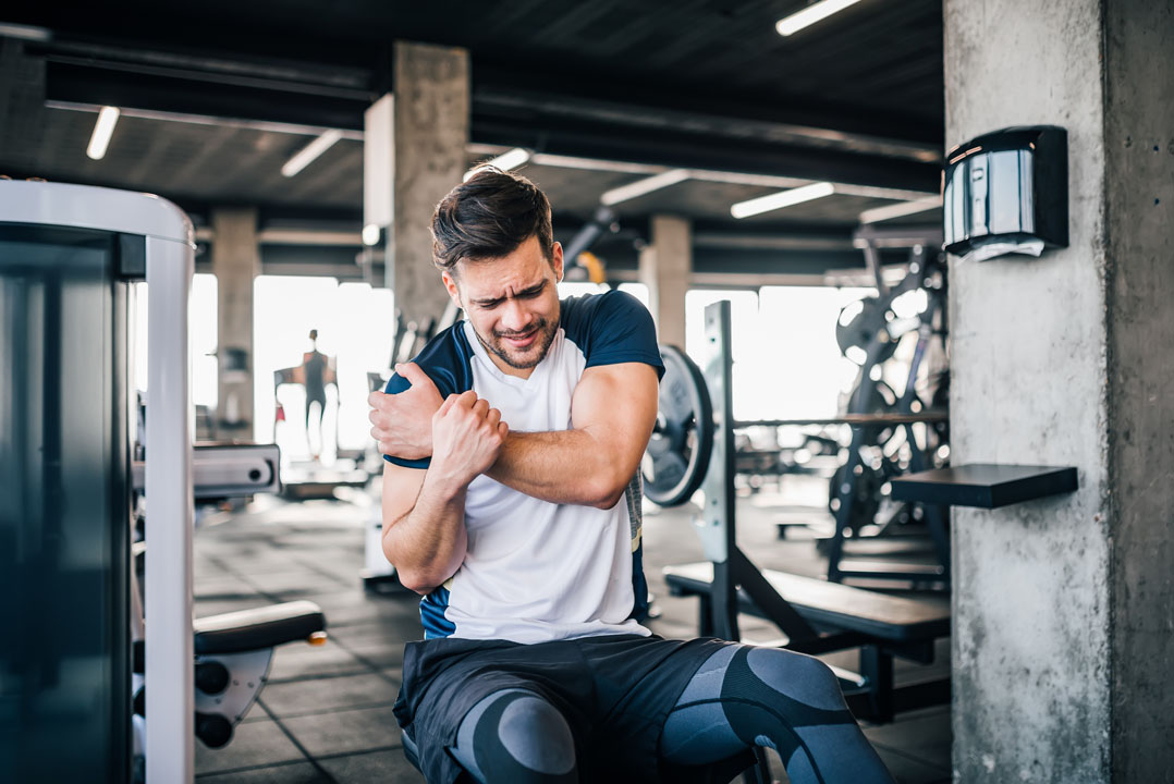 man working out in gym grabbing his shoulder from a sport injury