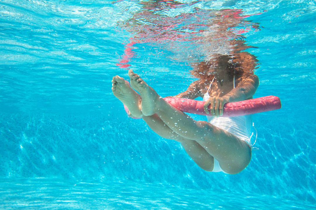 woman doing water aerobics in a pool with a pool noodle