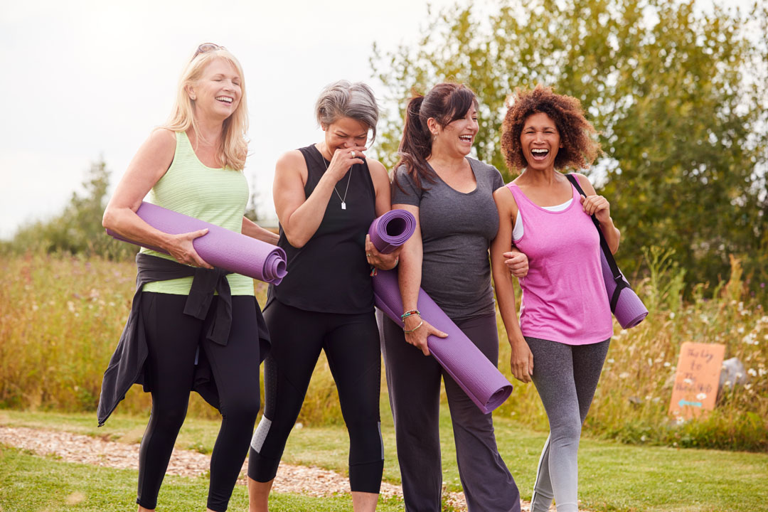 group of four women going to outdoor yoga class