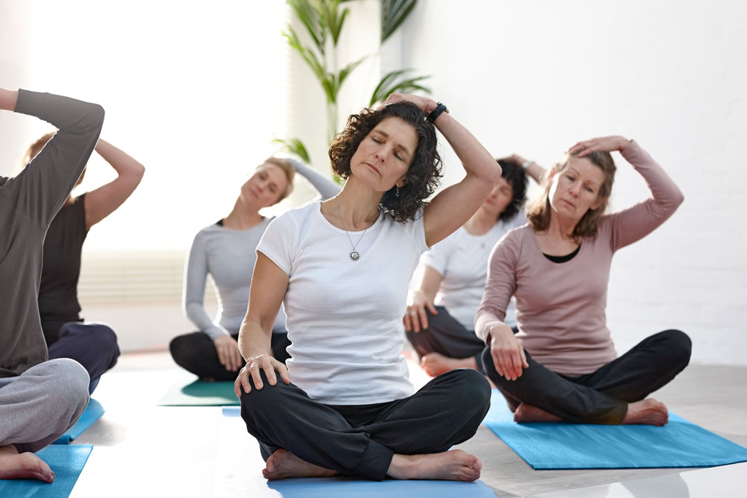 mature women in exercise class doing a neck stretch exercise