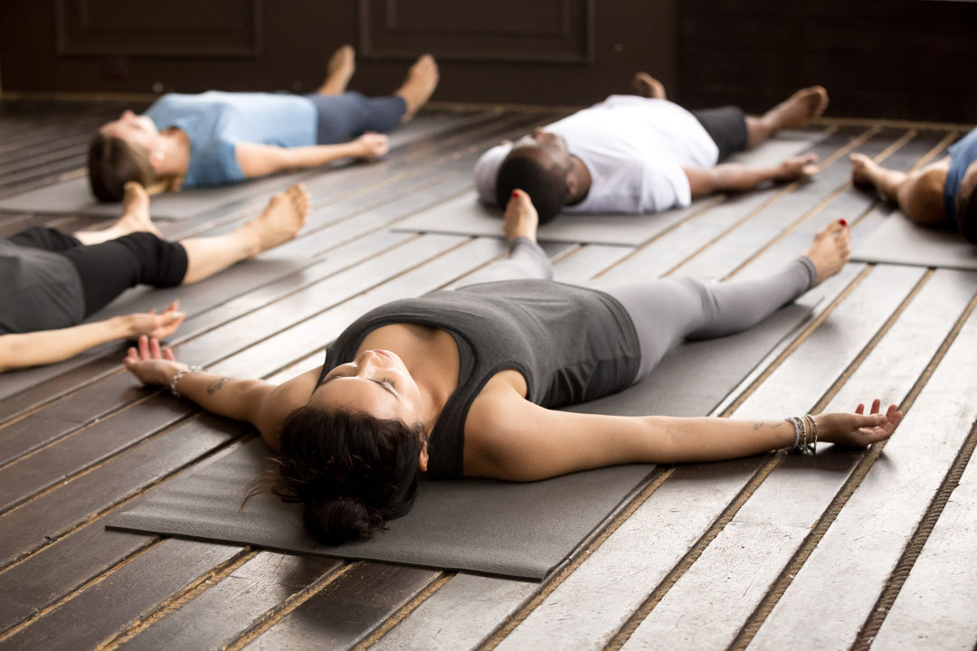 group of diverse women and men doing Savasana, corpse pose, relaxation pose