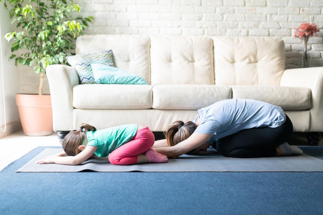 om y niña haciendo pose de niño - yoga - estiramiento del cuello