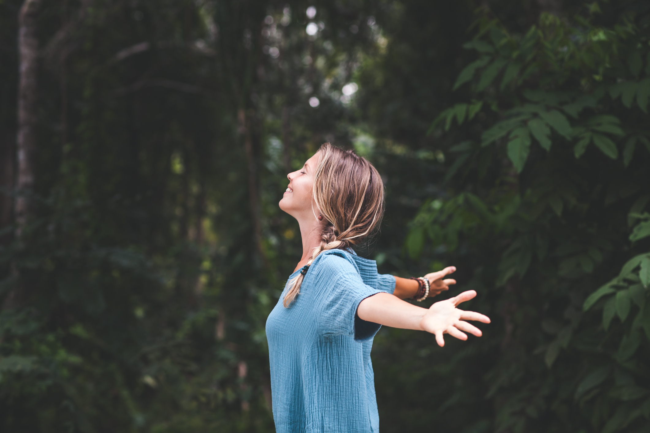 woman connecting with nature, arms wide, good posture