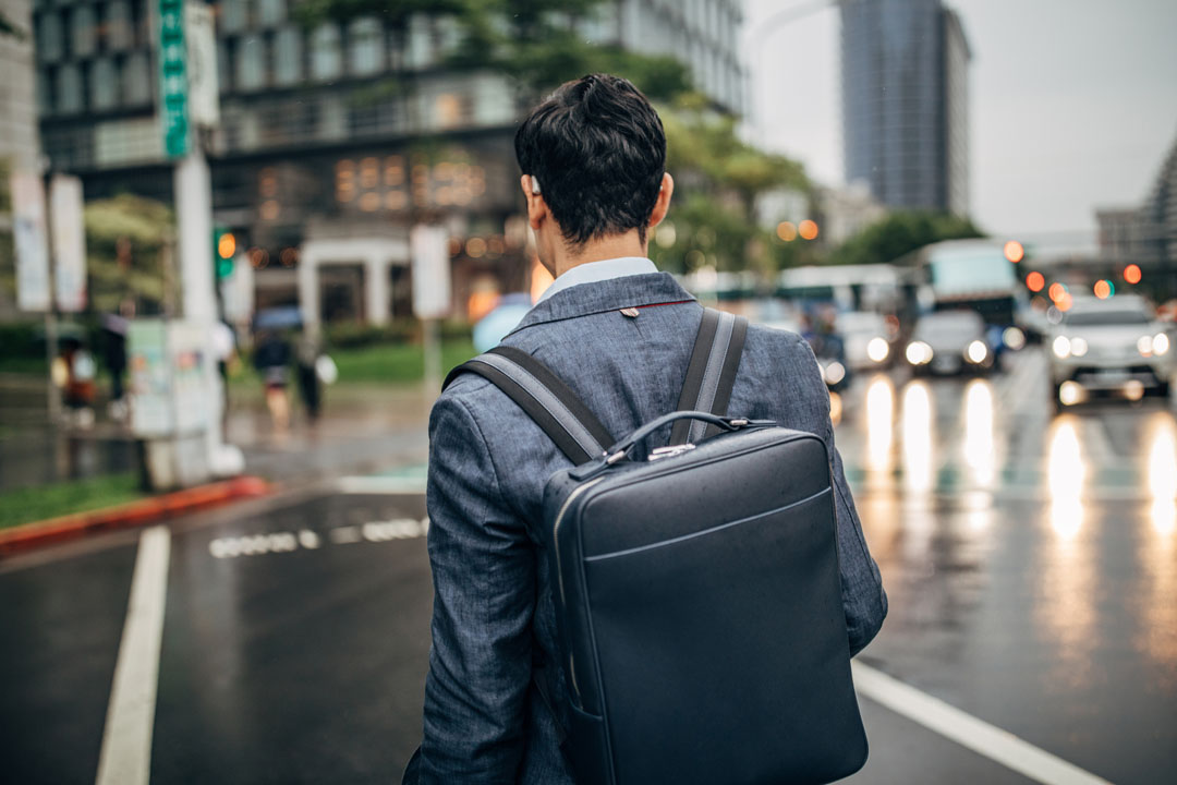 young businesses man carrying backpack style work bag