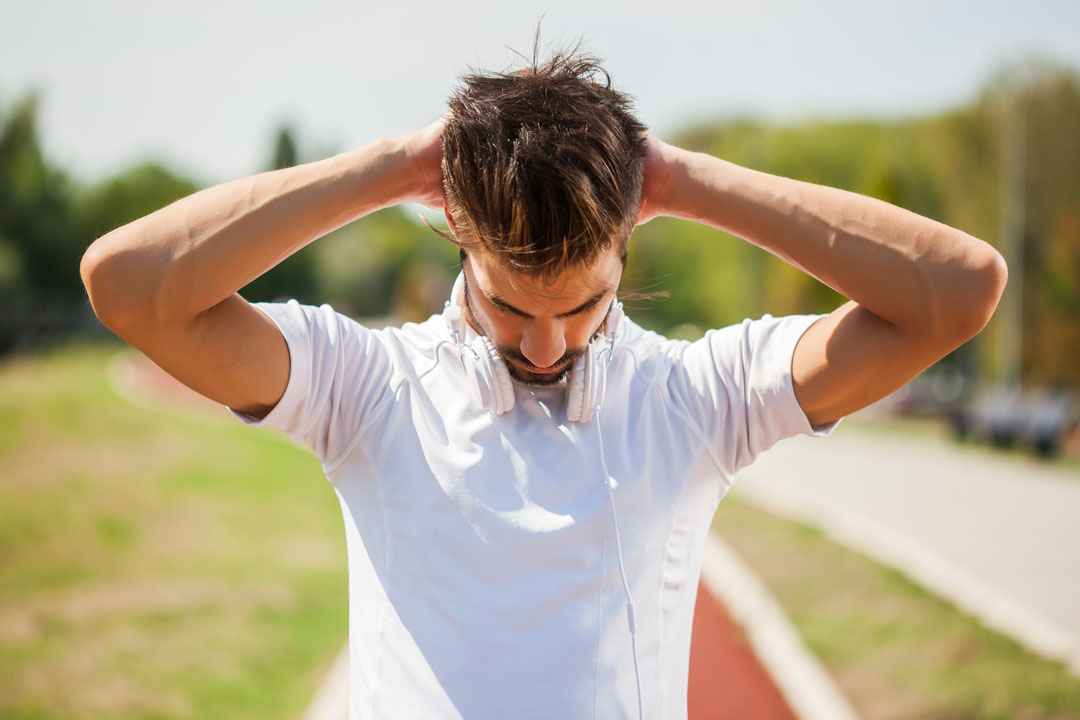 Young man is exercising on sunny day. He is stretching his neck.