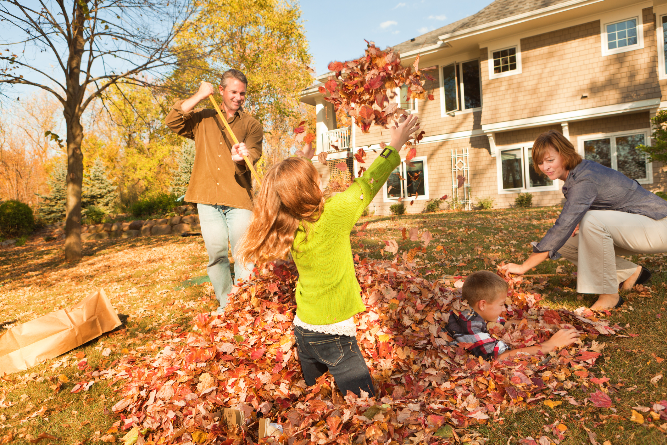 family raking leaves into a pile in the Fall