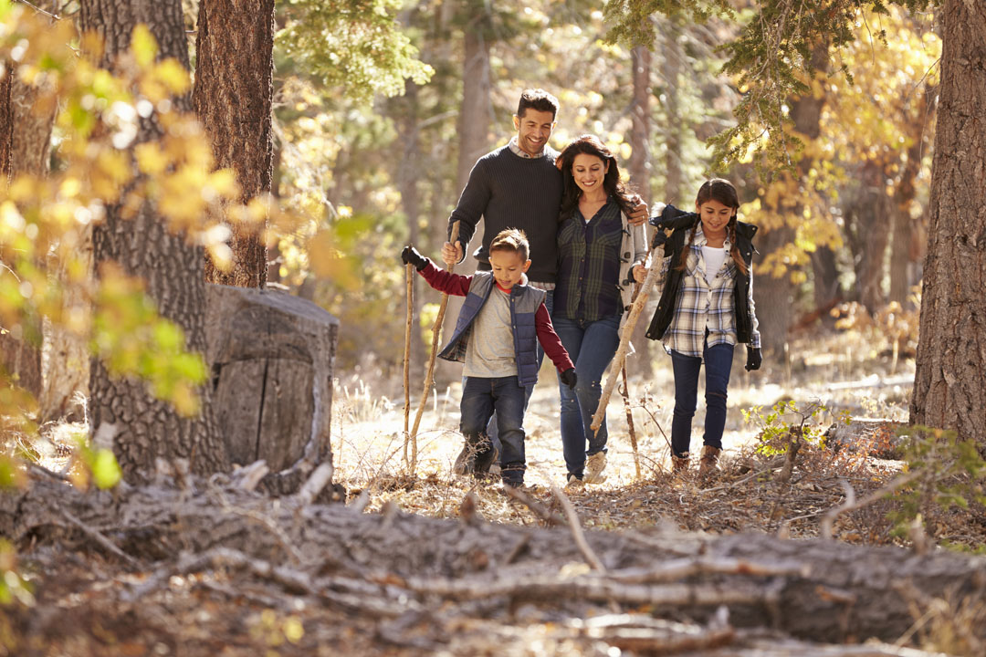 Happy Hispanic family with two children walking in a forest