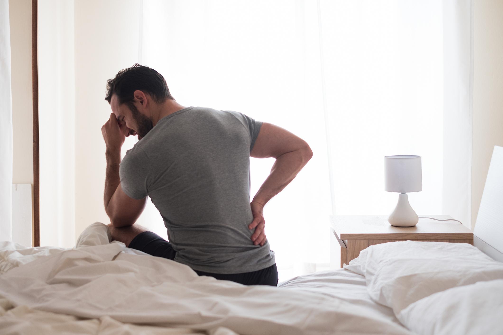El hombre se despierta por la mañana y sufre de dolor de espalda