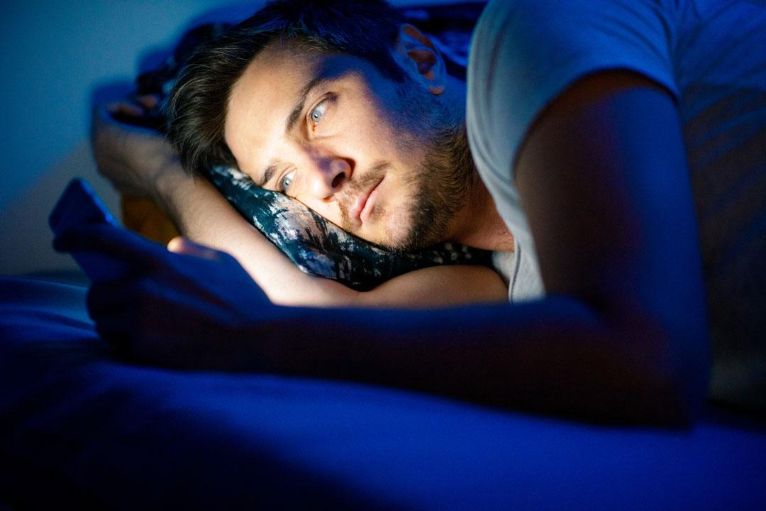 Joven con teléfono inteligente en la cama por la noche, copia espacio