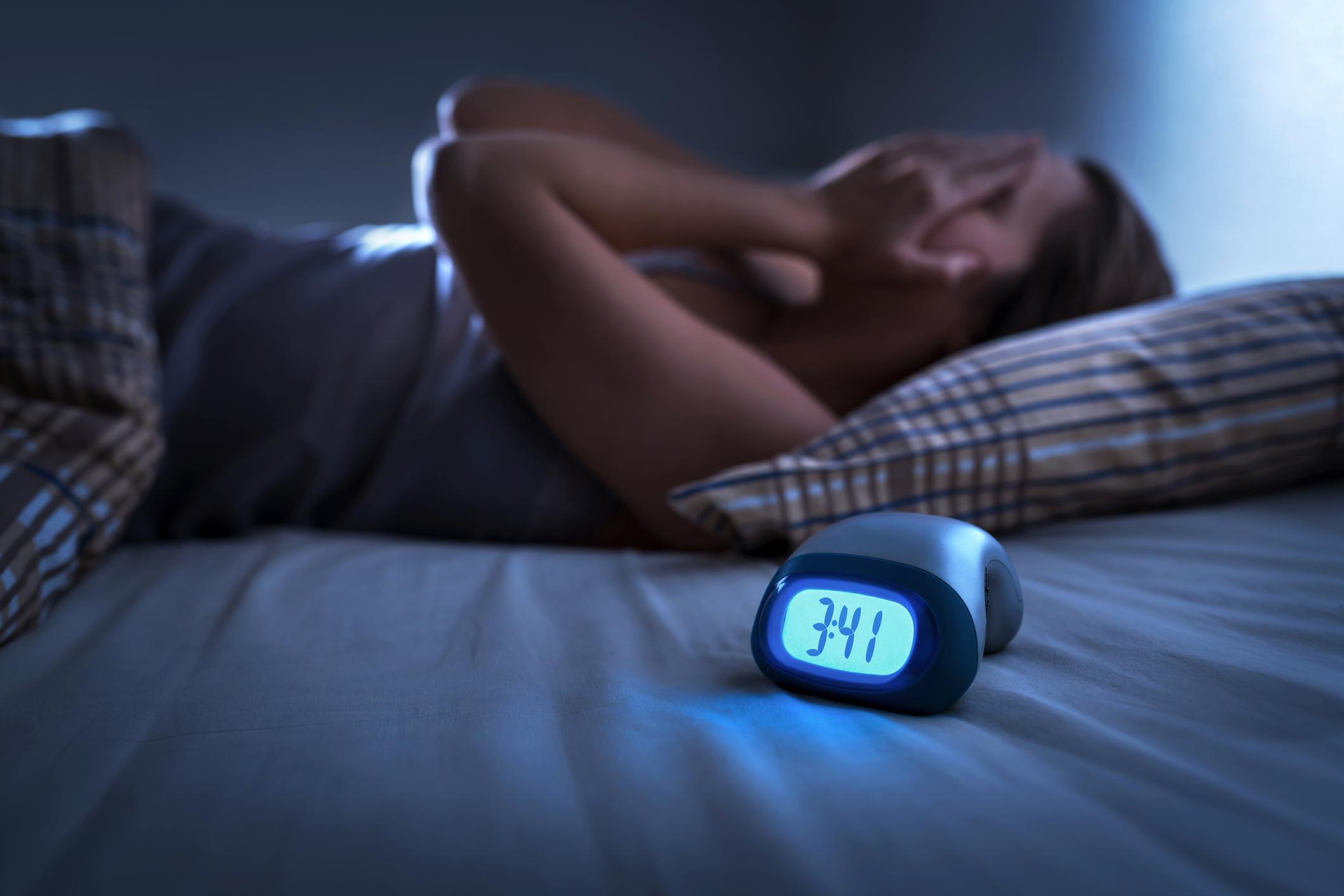 Mujer insomne que sufre de insomnio, apnea del sueño o estrés. Señora cansada y agotada. Dolor de cabeza o migraña. Despierto en medio de la noche. Persona frustrada con problema y reloj despertador que muestra la hora