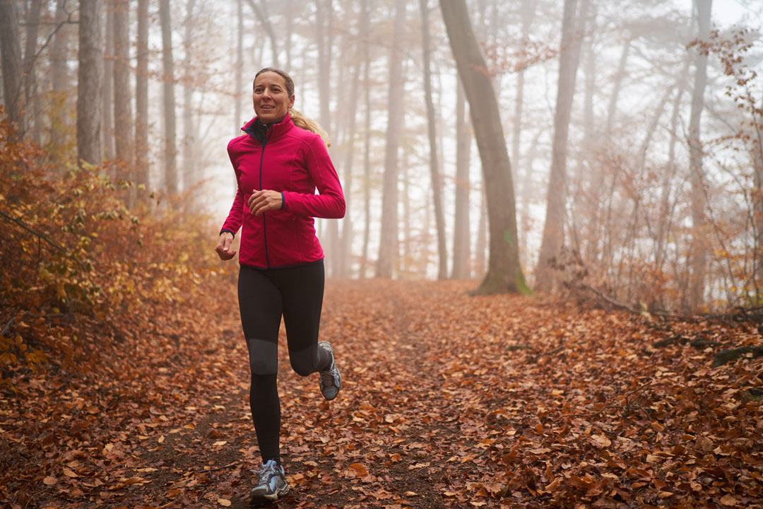 woman trail running in the fall