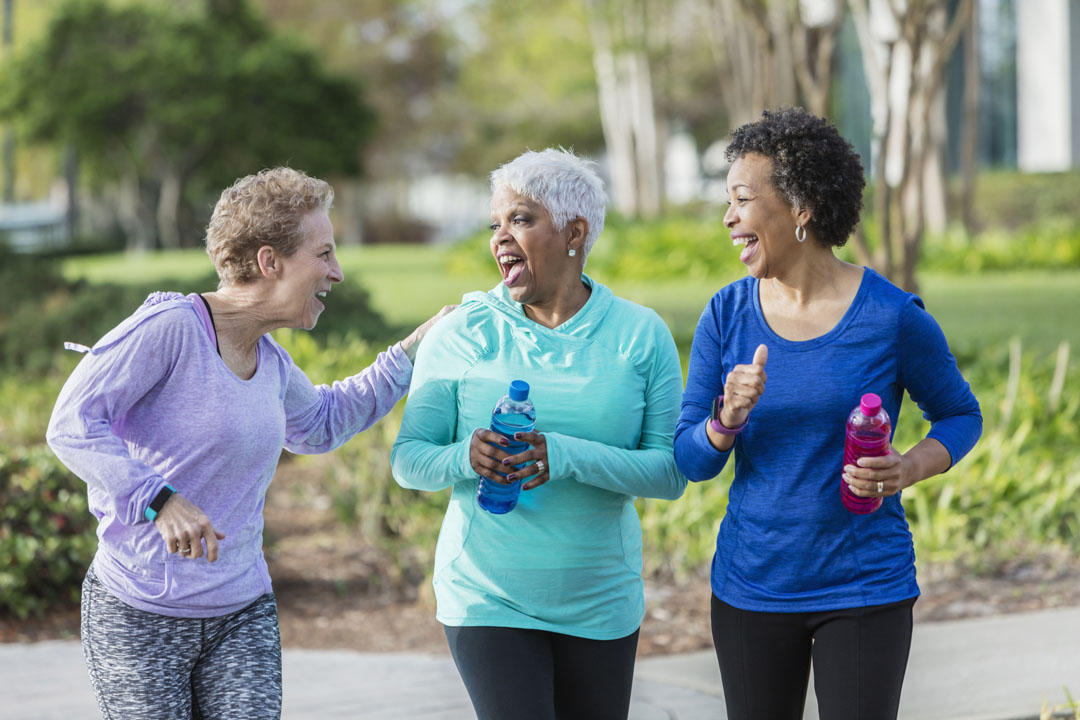 A group of three multi-ethnic women exercising in the park, talking and laughing as they power walk, carrying water bottles. The mature woman with black hair is in her 50s. Her friends are senior women in their 60s.