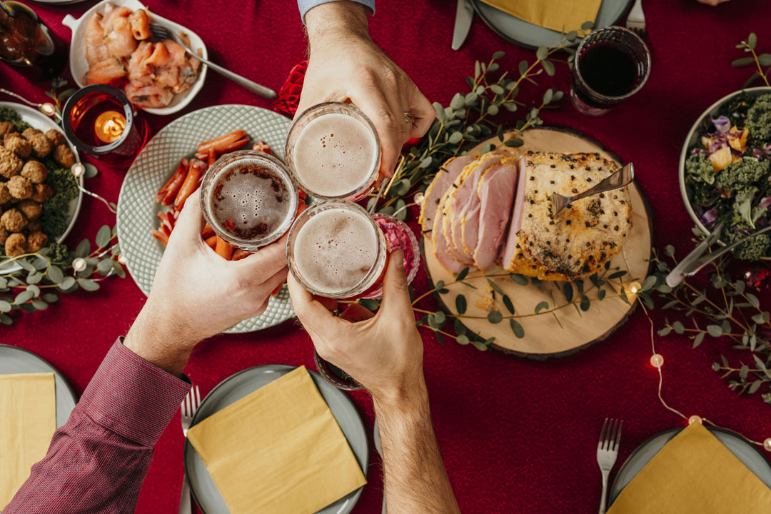 Christmas food smörgåsbord people toasting in beer - survive the holidays by grabbing a smaller plate