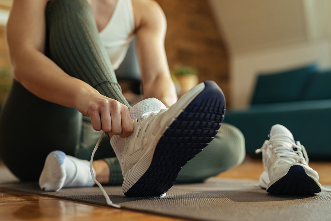 woman putting on sneakers to exercise