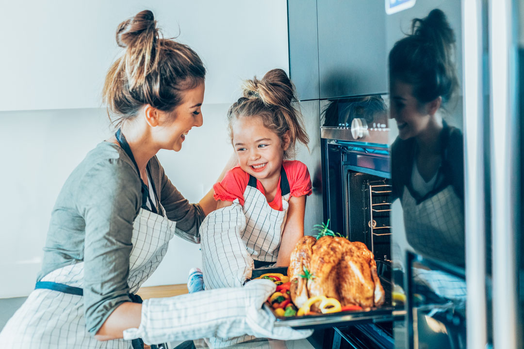 mother and daughter making a holiday turkey dinner