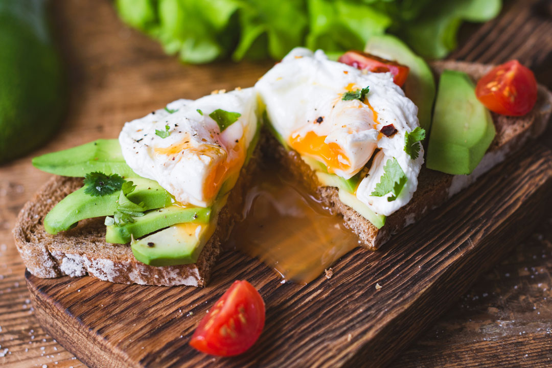 Tasty sandwich with poached egg and avocado