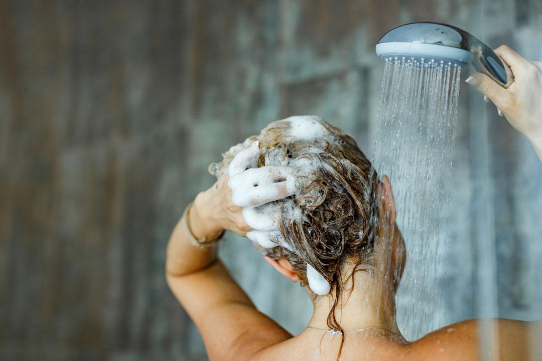 Vista posterior de una mujer lavándose el cabello con champú en el baño.