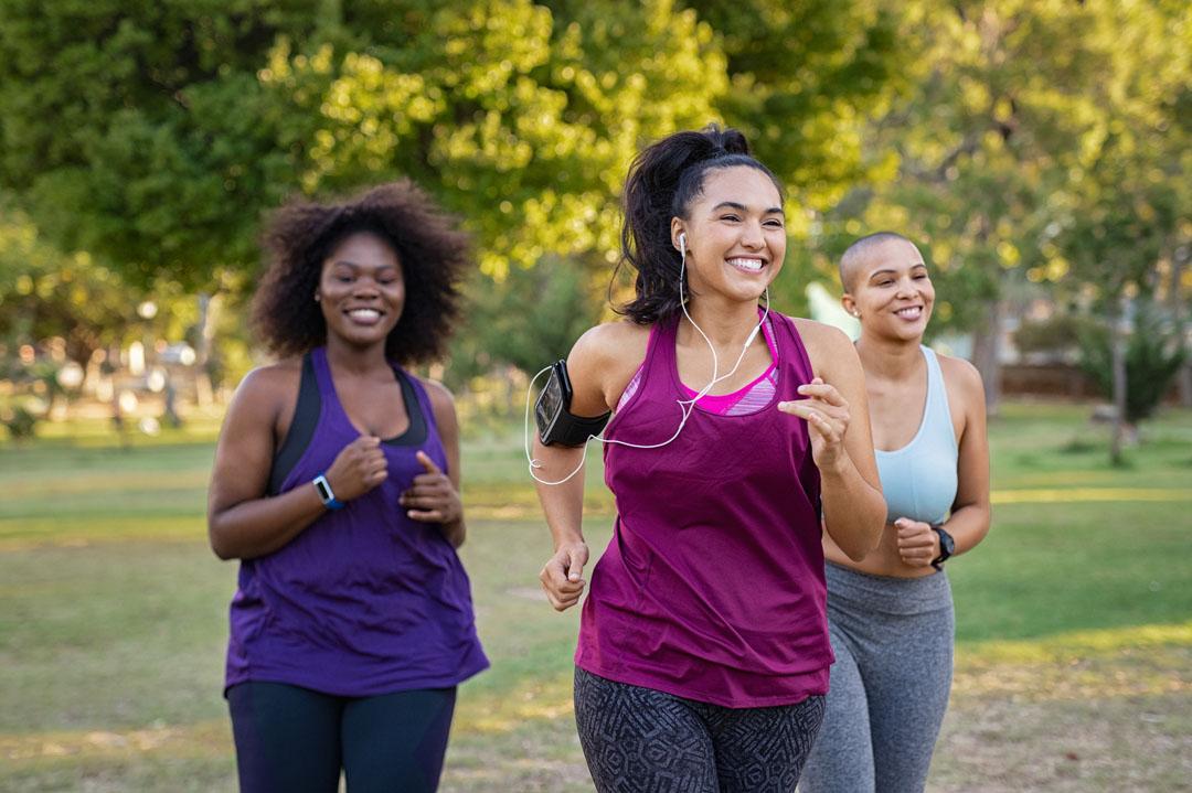 Grupo de amigos chicas con curvas trotar juntos en el parque. Hermosas mujeres jóvenes sonrientes corriendo en el parque en un día soleado. Corredoras escuchando música mientras trota. - consejos para motivarse a hacer ejercicio