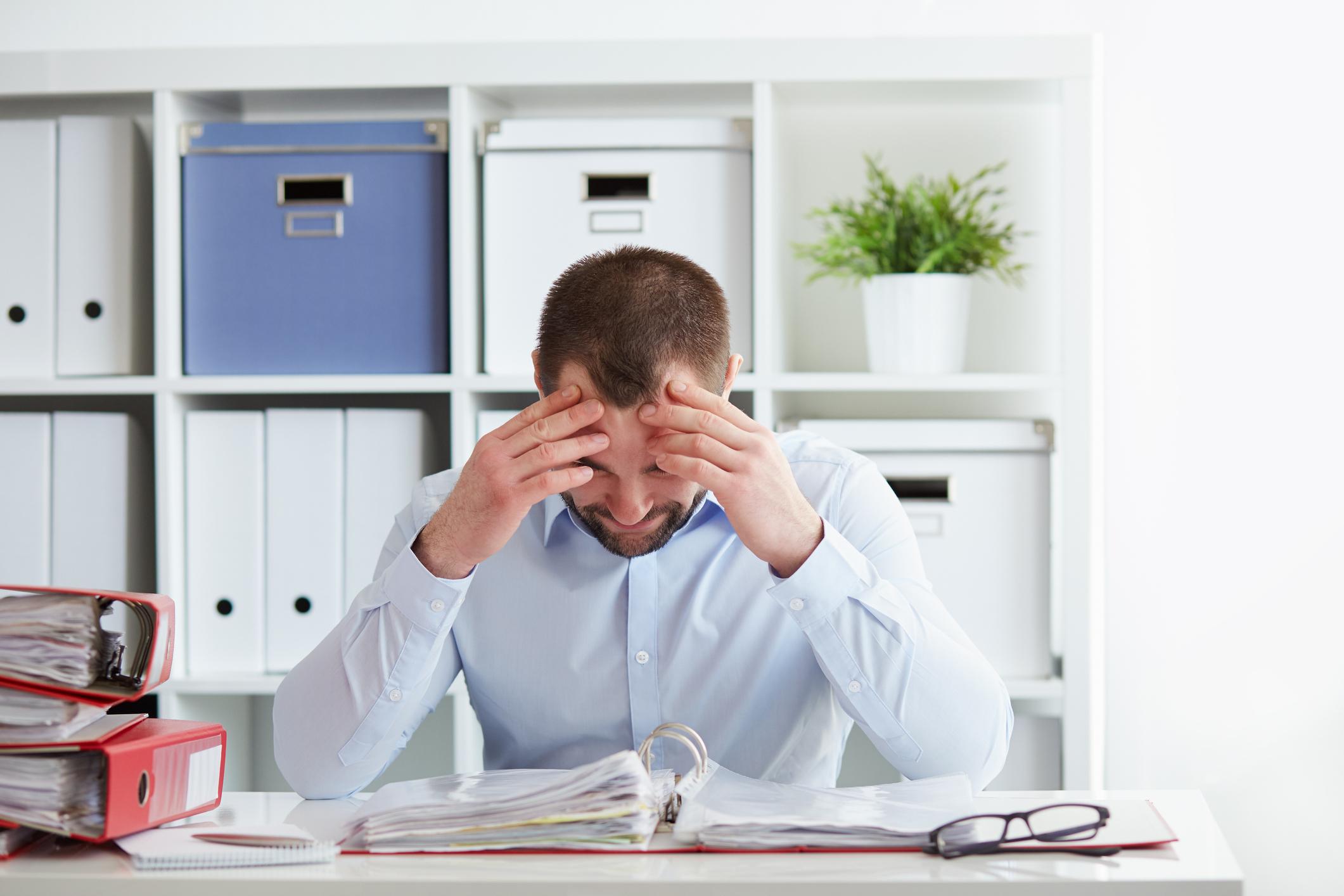 Hombre de negocios joven bajo estrés con dolor de cabeza y migraña - sentarse en el escritorio durante largos períodos de tiempo - razones para una depresión de la tarde