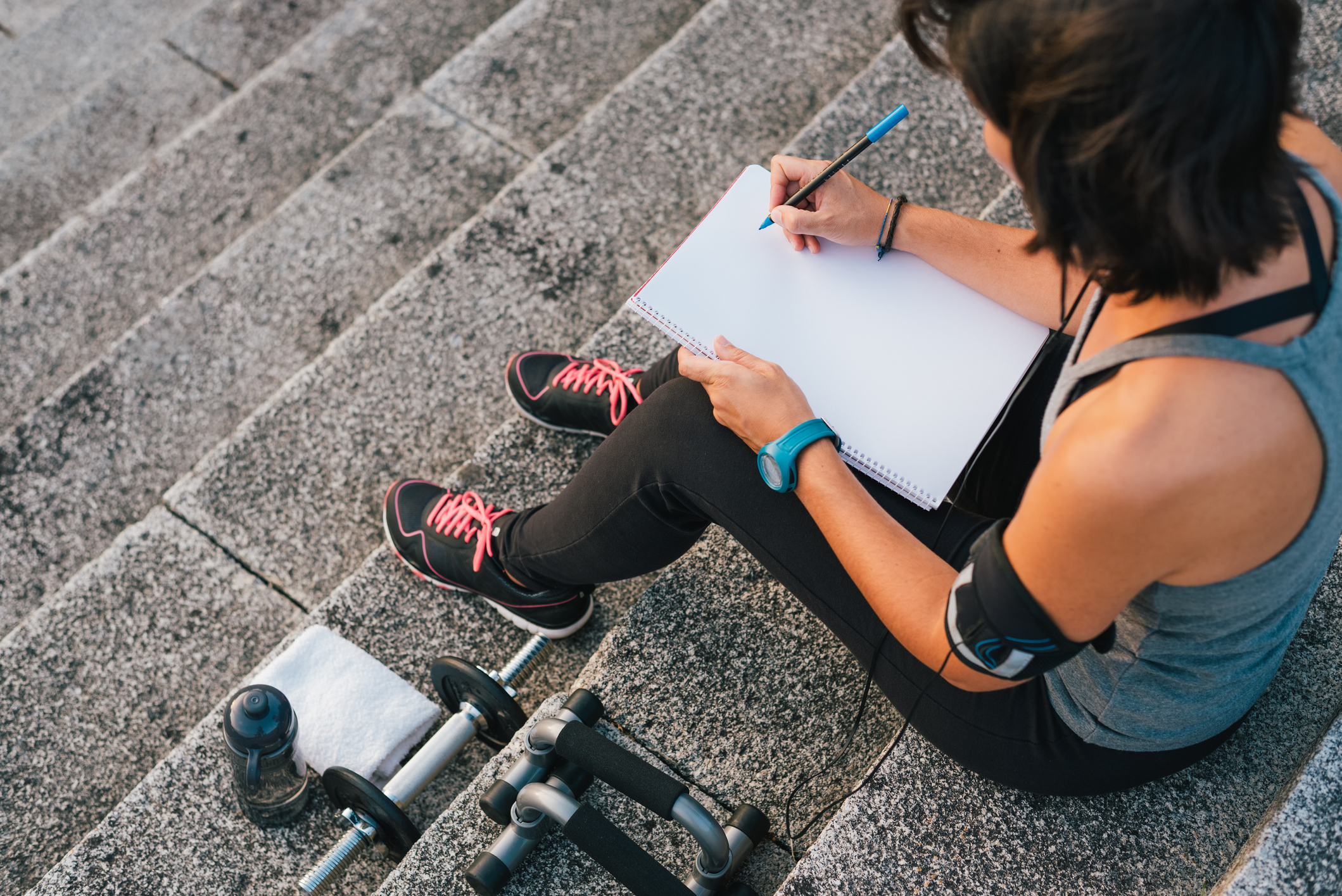 Fitness sporty woman writing on blank notepad while sitting on urban stone stairs before exercises workout routine. Female athlete focusing on her goals - tips to get motivated to exercise