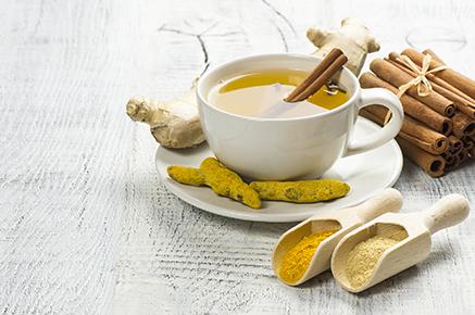 Té de hierbas de jengibre y cúrcuma en taza blanca con raíz de jengibre, cúrcuma seca, palitos de canela y su polvo. Té de especias de hierbas para los días fríos de invierno con gripe