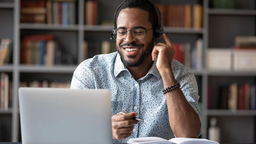 Sonriente hombre afroamericano en gafas y auriculares ver seminario web en portátil tomando notas, Feliz trabajador estudiante masculino birracial en auriculares de escritura a mano estudiando o trabajando usando la computadora