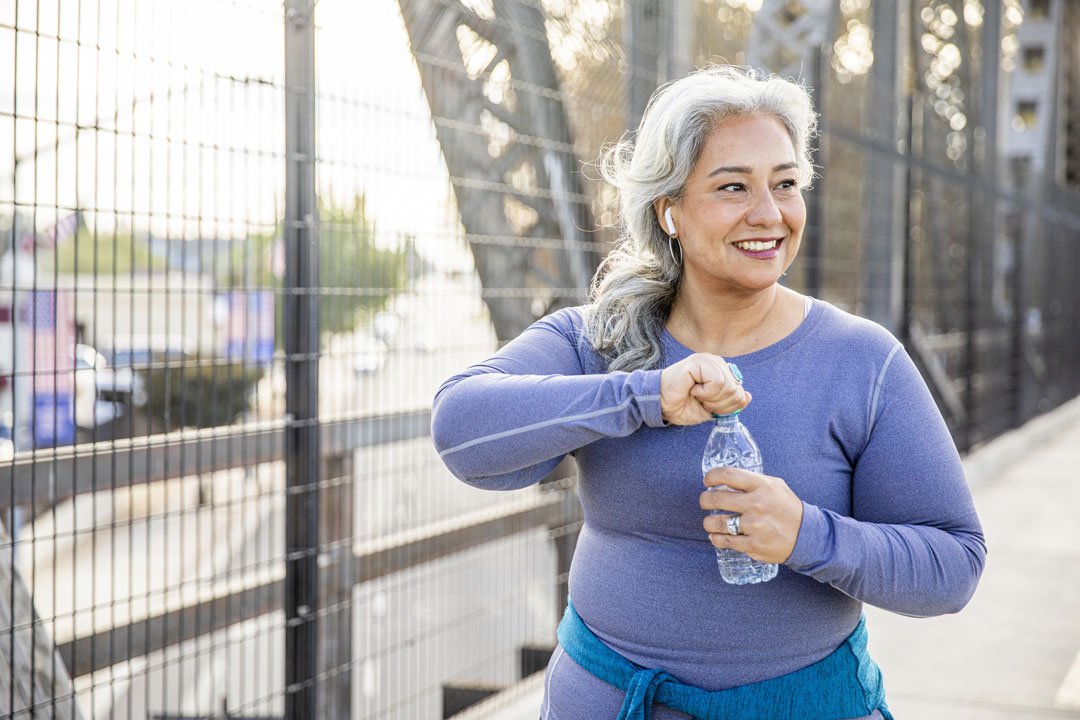 Una mujer mexicana senior de agua potable después de un entrenamiento