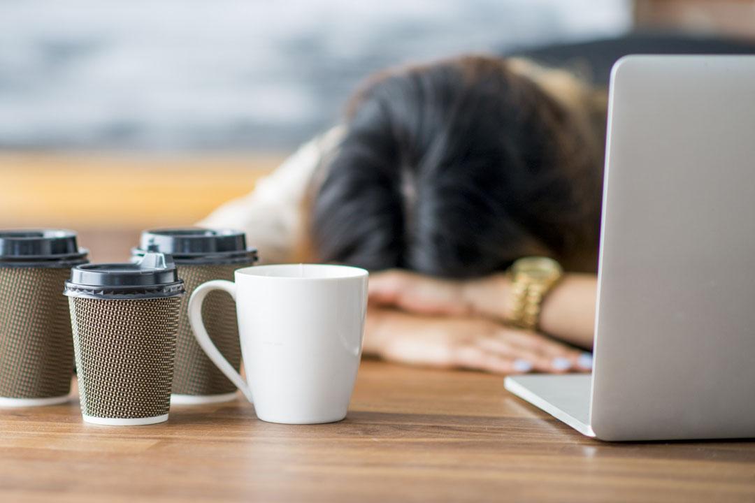 Una emprendedora y empresaria está trabajando en la puesta en marcha de su empresa en su oficina.. Se ha quedado dormida en la oficina con la cabeza apoyada en su escritorio.. Las tazas de café vacías están sobre la mesa.