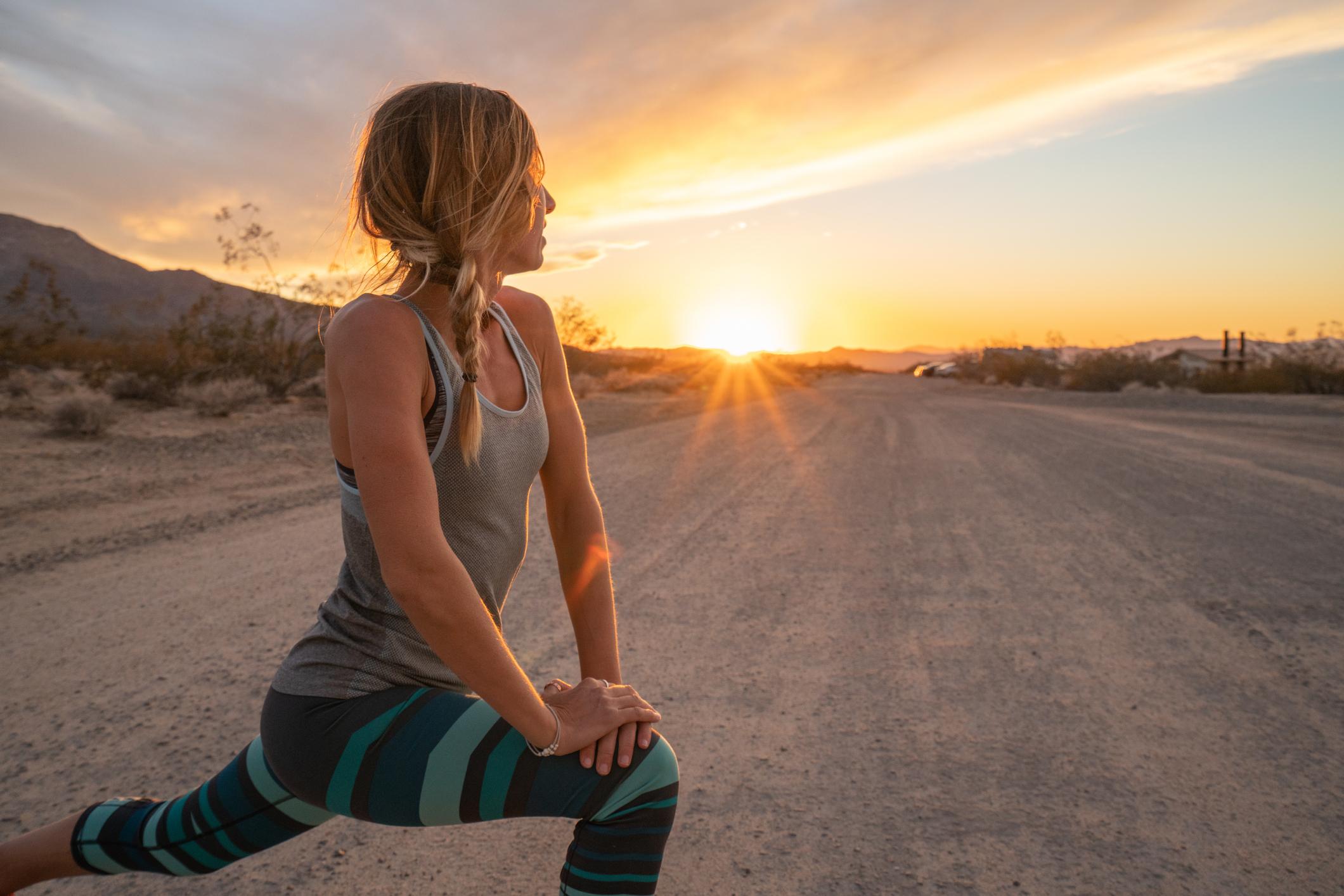 Mujer joven estirando el cuerpo después de trotar, puesta de sol al final del camino; mujer estira el cuerpo en la naturaleza, entrenamiento al aire libre