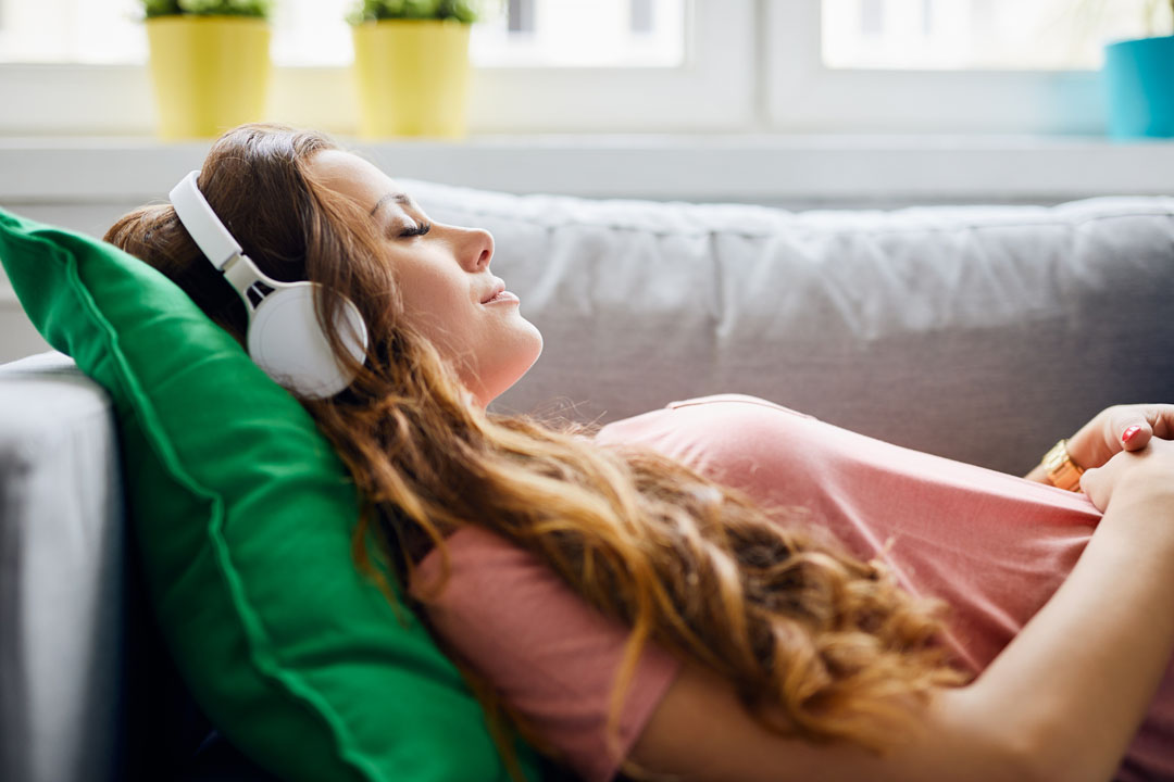 Portrait of a beautiful young woman lying on sofa with headphones on and closed eyes, relaxing - get motivated to exercise