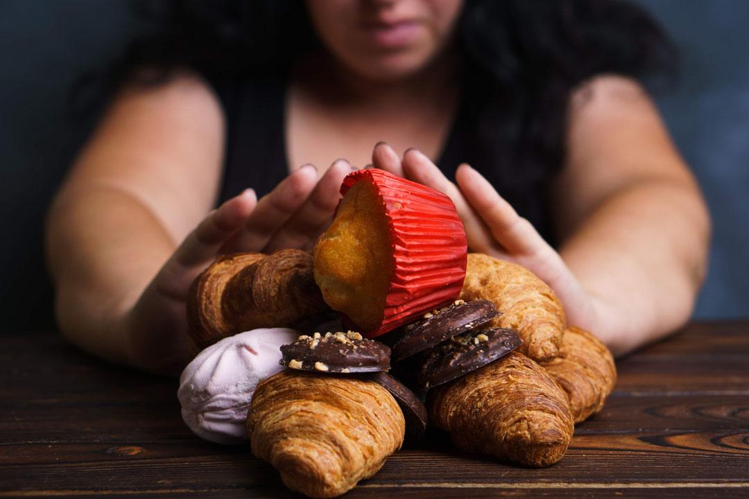Adicción al azúcar, opciones de nutrición, motivación y estilo de vida saludable. Retrato recortado de mujer con sobrepeso rechazando alimentos dulces - razones detrás de una depresión por la tarde
