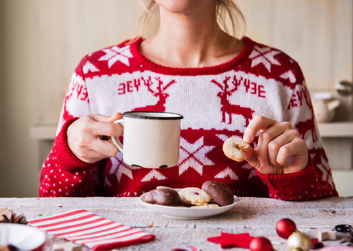 Woman in Holiday Sweater eating cookies and drinking hot chocolate