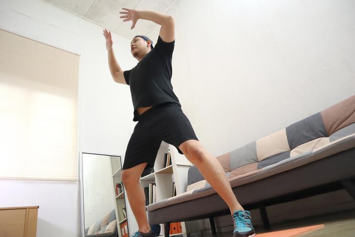 Hombre asiático haciendo ejercicio en casa para mantenerse saludable en un nuevo estilo de vida normal, concepto de entrenamiento en casa interior, entrenamiento de circuito de cardio con peso corporal - ejercicios de hiit